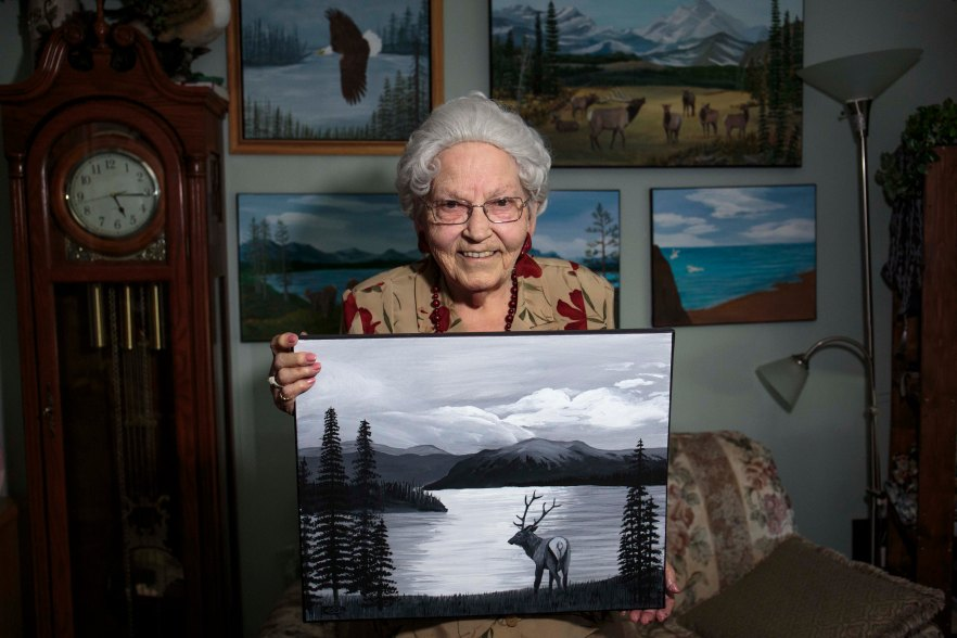"Ruth Cook, 94, shows off her black and white painting at the Pine Valley Seniors Lodge on Aug. 15. Cook started painting in 2009 one year after her husband passed away. ""I'll keep painting as long as God has me here,"" she laughs."